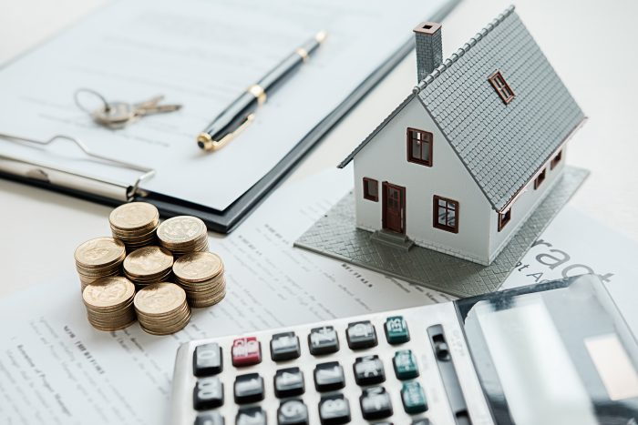Coins, small house, calculator and notepad with pen on the table